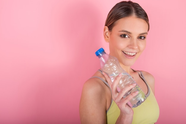 水分補給、健康的なライフスタイルのコンセプトを維持します。スポーツを着て水筒を保持している女性モデル