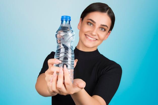 Оставаться гидратированной водой - это концепция жизни, хорошие привычки здорового образа жизни. женщина держит бутылку с водой