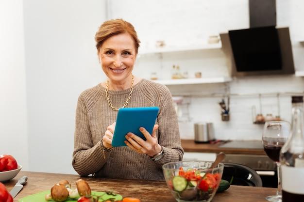 キッチンにいる。タブレットで情報を確認し、夕食を調理しながら笑顔の元気なフィット成熟した女性