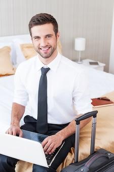 Оставаться на связи всегда и везде. вид сверху красивого молодого человека в рубашке и галстуке, работающего на ноутбуке и улыбающегося, сидя на кровати в гостиничном номере
