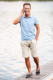 어디서나 연락을 유지합니다. 부두를 따라 걷는 동안 휴대 전화로 이야기하고 웃는 행복한 성숙한 남자의 전체 길이