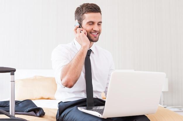 Оставаться на связи с коллегами. красивый молодой человек в рубашке и галстуке работает на ноутбуке и разговаривает по мобильному телефону, сидя на кровати в гостиничном номере