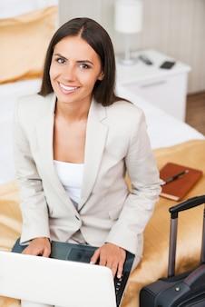 Оставаться на связи с моими коллегами. вид сверху красивой молодой деловой женщины в костюме, работающей на ноутбуке и улыбающейся, сидя на кровати в гостиничном номере