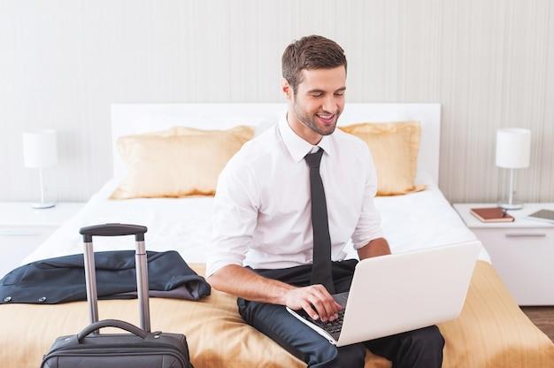 Оставаться на связи с офисом. красивый молодой человек в рубашке и галстуке работает на ноутбуке и улыбается, сидя на кровати в гостиничном номере
