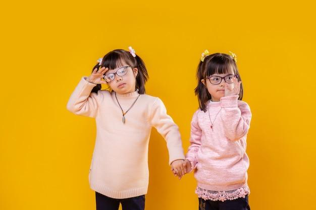 함께있어. 다운 증후군을 앓고있는 멋진 어린 아이들이 사진 모델이되고 노란색 벽 앞에 머물러 있습니다.