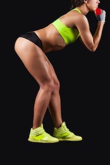 調子を保つ。ダンベルで筋力トレーニングをしている若い女性