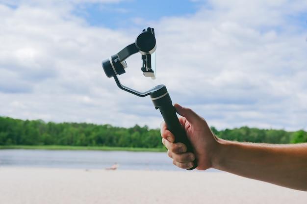 남자의 손에 스마트폰이 있는 스테디캠. 하늘과 해변을 배경으로.