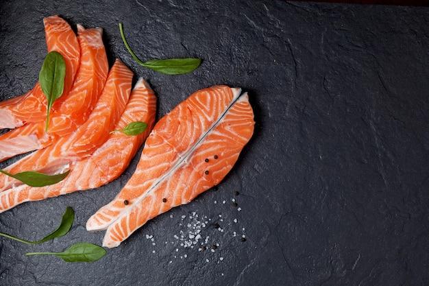 黒い石の上にほうれん草の葉で飾られたステーキと鮭の切り身上面図コピースペース