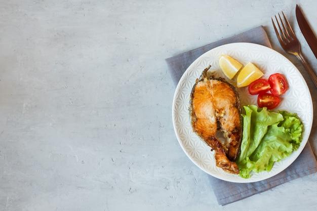 Стейк из запеченной лососевой рыбы на тарелке со свежими овощами.