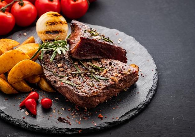 Стейк из говядины. стейк из говядины среднего размера с красным перцем, ароматными травами и жареным луком