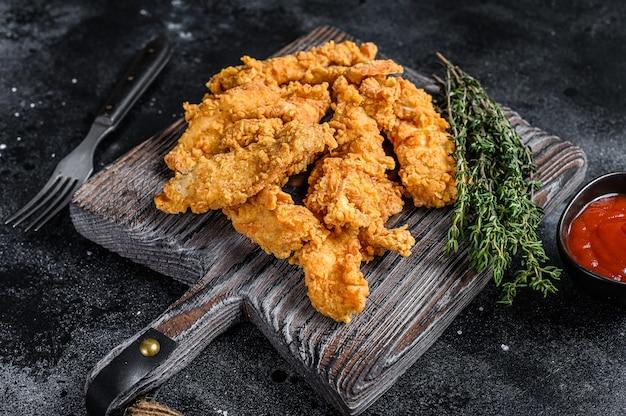 ステーキフィンガーはパン粉をまぶした鶏の胸肉のストリップを揚げました。黒の背景。上面図。