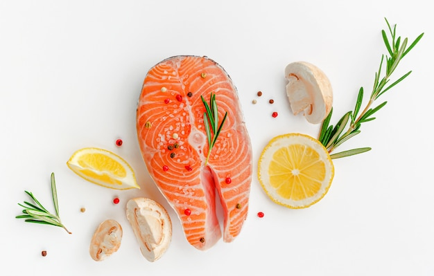 Steak of fresh salmon fish with mushrooms, rosemary and lemon top view, keto diet concept.