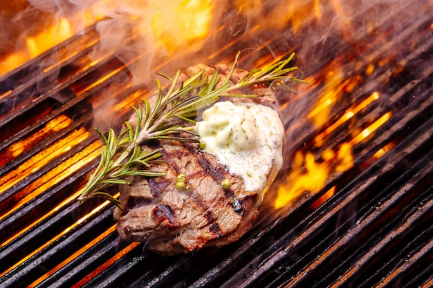 Steak on a grill fire, with herbs and butter