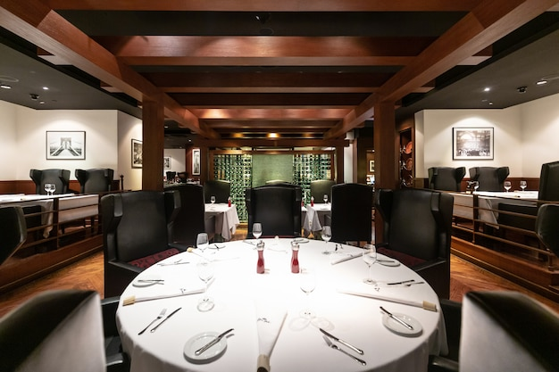 Steak house restaurant interior design with contemporary luxury furniture in new york style, elegant black leather chairs. deluxe, spacious and comfortable fine dining place.