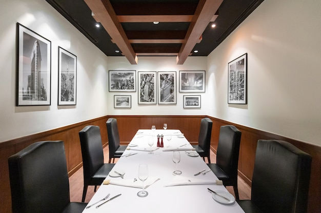 Steak house restaurant interior design with contemporary luxury furniture in new york style, elegant black leather chairs. deluxe, spacious and comfortable fine dining