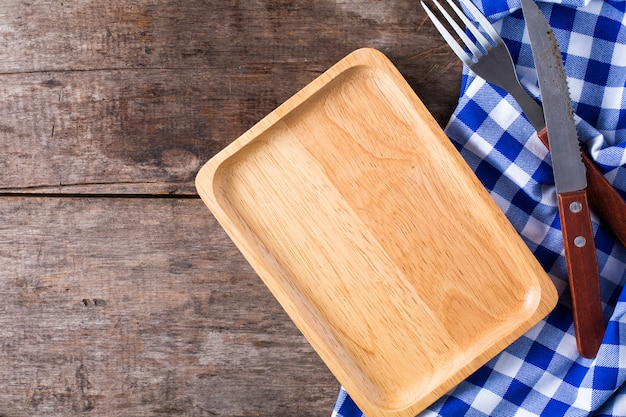 Steak knife and a fork with blue table cloth on wooden background