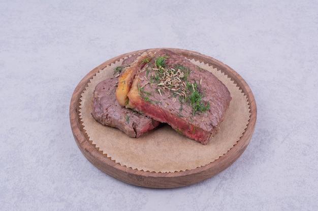 Fette di carne bistecca con erbe e spezie su una tavola di legno.