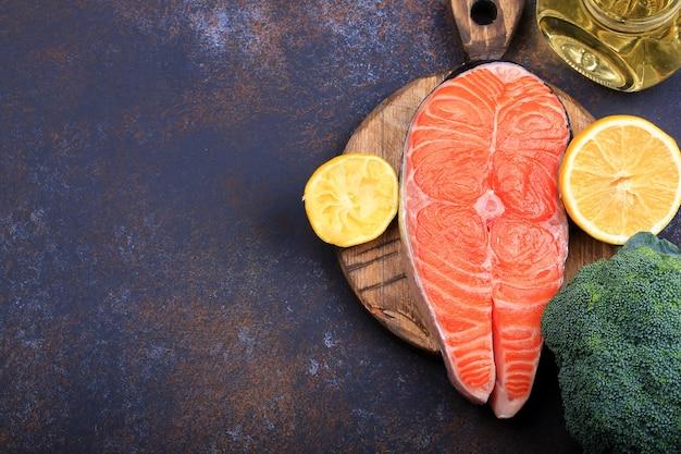 Стейк из сырого лосося с лимоном и оливковым маслом на темном фоне вид сверху.