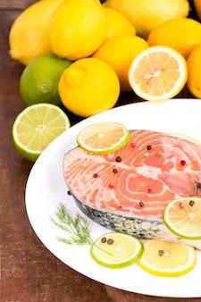 Стейк из красной рыбы и нарезанных лимонов на деревянном столе