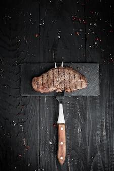 Стейк на вилке на темном деревянном фоне. баннер, место рецепта меню для текста, вертикальное изображение вида сверху.