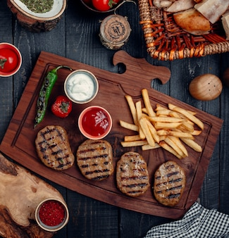 Steak pieces with french fries, grilled pepper and tomato, and sauces on a wooden board.