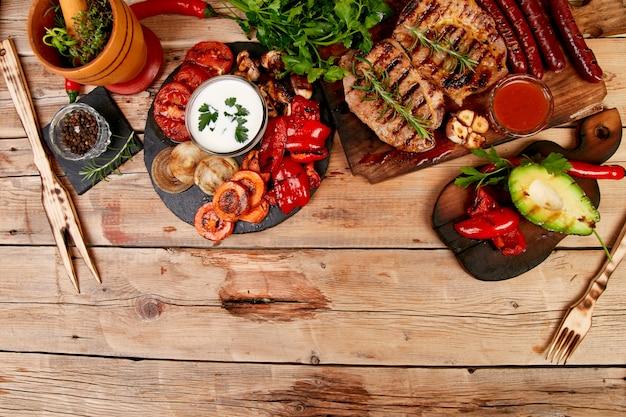 Стейк из свинины на деревянной разделочной доске с различными овощами гриль