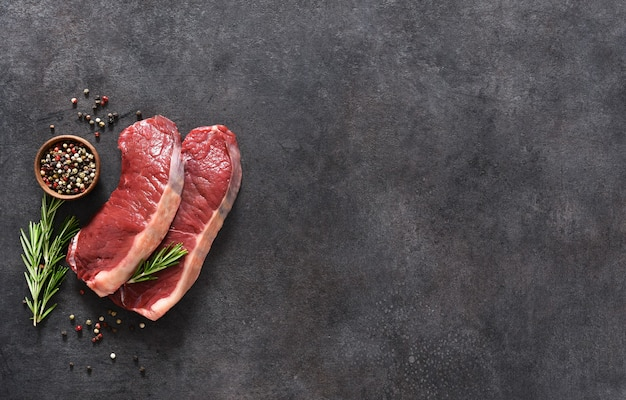 ステーキ、黒のコンクリートの背景にスパイスとローズマリーと生の牛肉。上からの眺め。