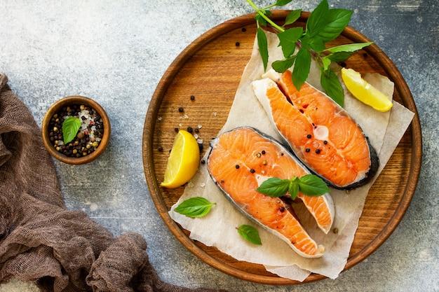 スレートテーブルの上にバジルとスパイスを使ってサーモンを調理するために準備されたステーキ生の魚上面図フラットレイ