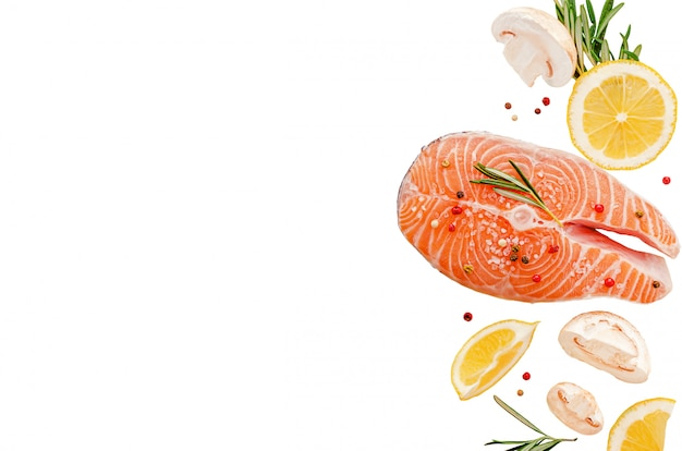 Steak of raw fresh salmon fish with mushrooms, rosemary and lemon isolated on white. top view, keto diet and healthy eating concept. copy space