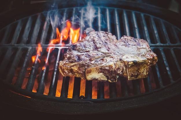 Стейк риби блэк ангус полоски на гриле дым паровая жарка на углях. большой кусок сырого мяса от говядины до черной металлической решетки для жарки