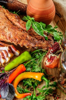 Steak on ribs,baked and served with color chili pepper. wooden rustic background. top view.