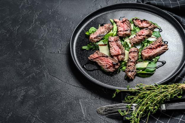 시금치, 아루 굴라, 슬라이스 쇠고기 스트립로 인 스테이크를 곁들인 스테이크 샐러드.