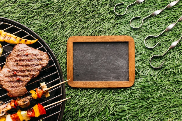 Steak and sausages grilling on barbecue gill near blank slate and metallic skewer over grass mat