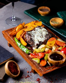 Steak served with potatoes grilled vegetable salad and sauce