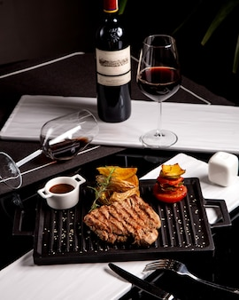 Steak served with potatoes, grilled vegetables, sauce and wine