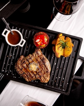 Steak served with potatoes grilled vegetables sauce and wine