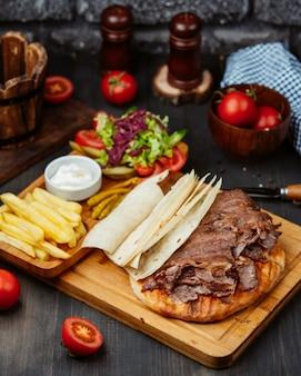 Ломтики стейка сверху лаваш, картофель фри, свежий салат и майонез
