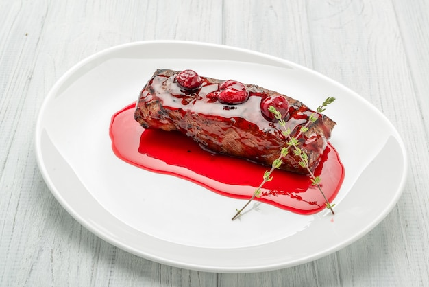 Steak with cherry sauce on a white plate