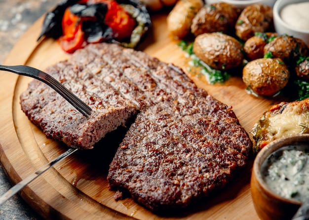 Steak with fried potatoes and vegetables on wooden board