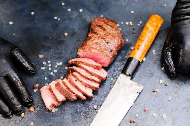 Стейк-хаус. стейк стриплойн. нарезанное мясо говядины на гриле и нож.