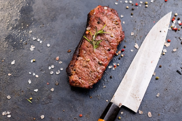Стейк-хаус. стейк стриплойн. вид сверху жареного говяжьего мяса и ножа.