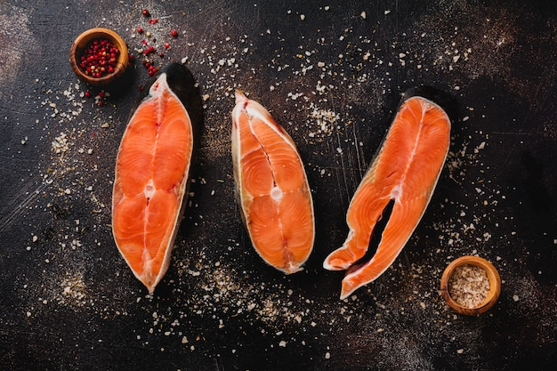 Steaks of chum salmon raw with spices, herbs, salt and lemon on old stone surface