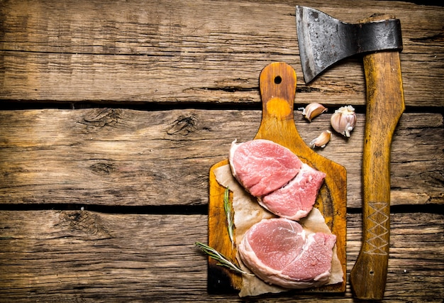 Стейки из сырого мяса, чеснок с топором. на деревянном фоне. свободное место для текста. вид сверху
