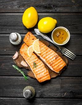 Стейки из лосося на гриле с дольками лимона. на деревянном.