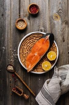 Стейки кеты сырые со специями, зеленью, солью и лимоном на старой деревянной поверхности