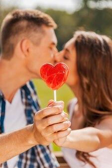 롤리팝 뒤에서 키스를 훔치는 것. 둘 다 야외에 서 있는 동안 붉은 심장 모양의 롤리팝 뒤에 숨어 사랑하는 커플