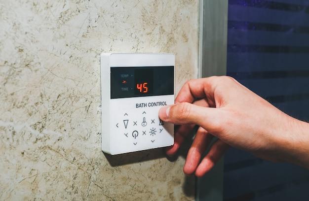 サウナのスチームバス制御装置。男は指でハマムの温度を調節しています。自由な時間とリラックスしたコンセプト。