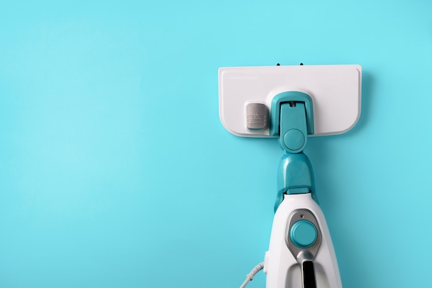 Steam cleaner mop on blue background.
