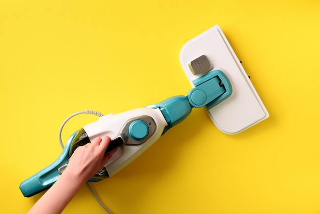 Steam cleaner mop on yellow background.
