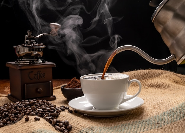 グランジウッドテーブルの背景に黄麻布ヘシアンの上にグラインダー、ローストビーンズ、コーヒー挽いた、やかんとスチームコーヒーカップ
